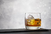 Close-up whiskey with ice cubes on gray background with copy space