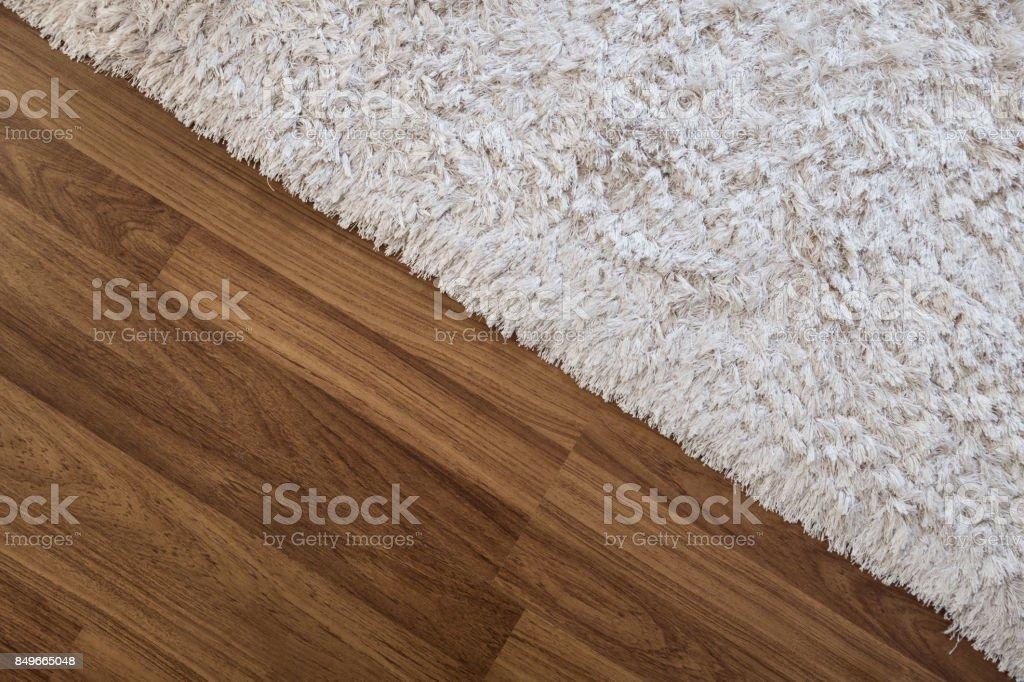 Close-up white carpet on laminate wood floor in living room, interior decoration stock photo