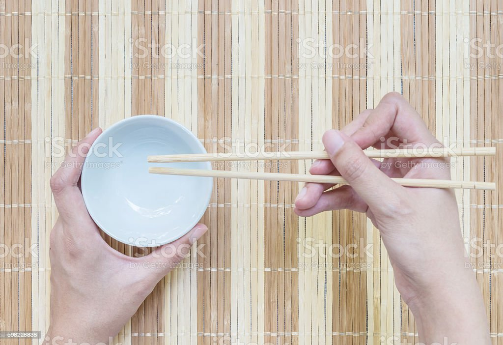Closeup white ceramic chalice with wood chopsticks in woman hand foto royalty-free