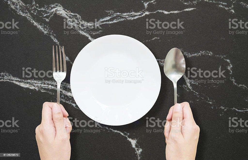 Closeup white ceramic dish on black marble stone stock photo