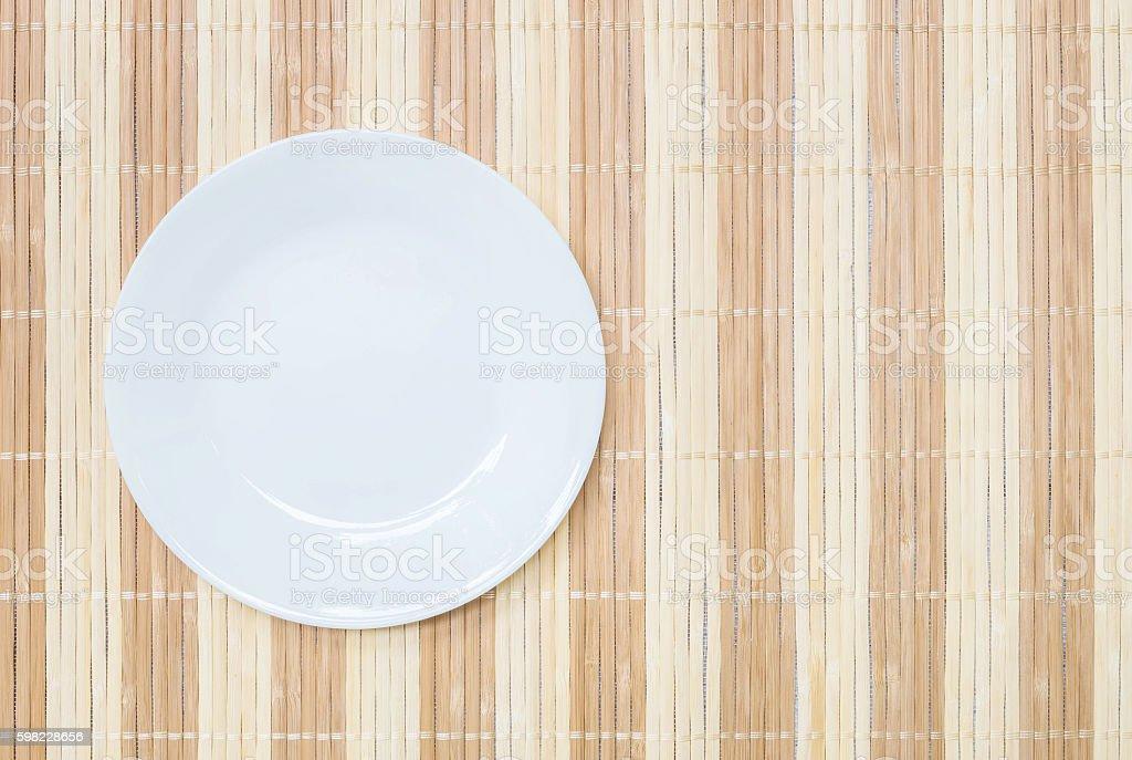 Closeup white ceramic dish on wood mat foto royalty-free