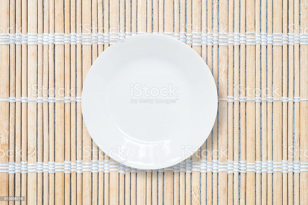 Closeup white ceramic dish on wood mat textured background stock photo