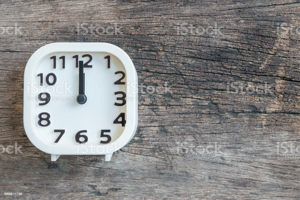 Closeup white clock for decorate in 12 o'clock on old wood floor textured background with copy space stock photo