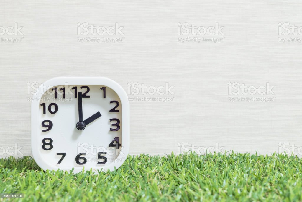 Closeup white clock for decorate in 2 o'clock on green artificial grass floor and cream wallpaper textured background with copy space Стоковые фото Стоковая фотография
