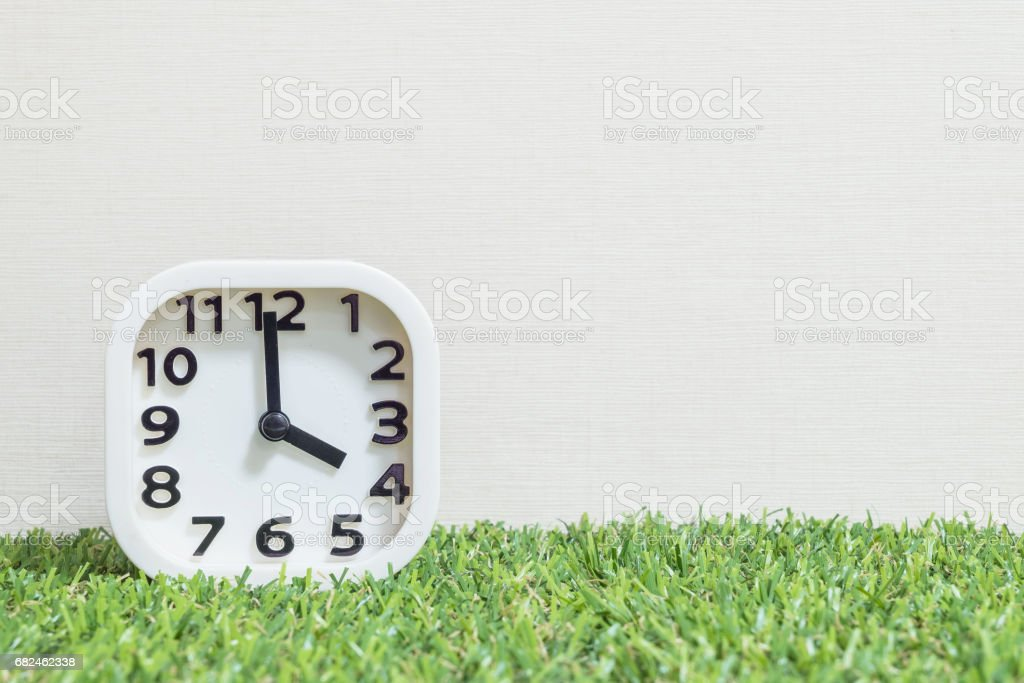 Closeup white clock for decorate in 4 o'clock on green artificial grass floor and cream wallpaper textured background with copy space royalty-free stock photo