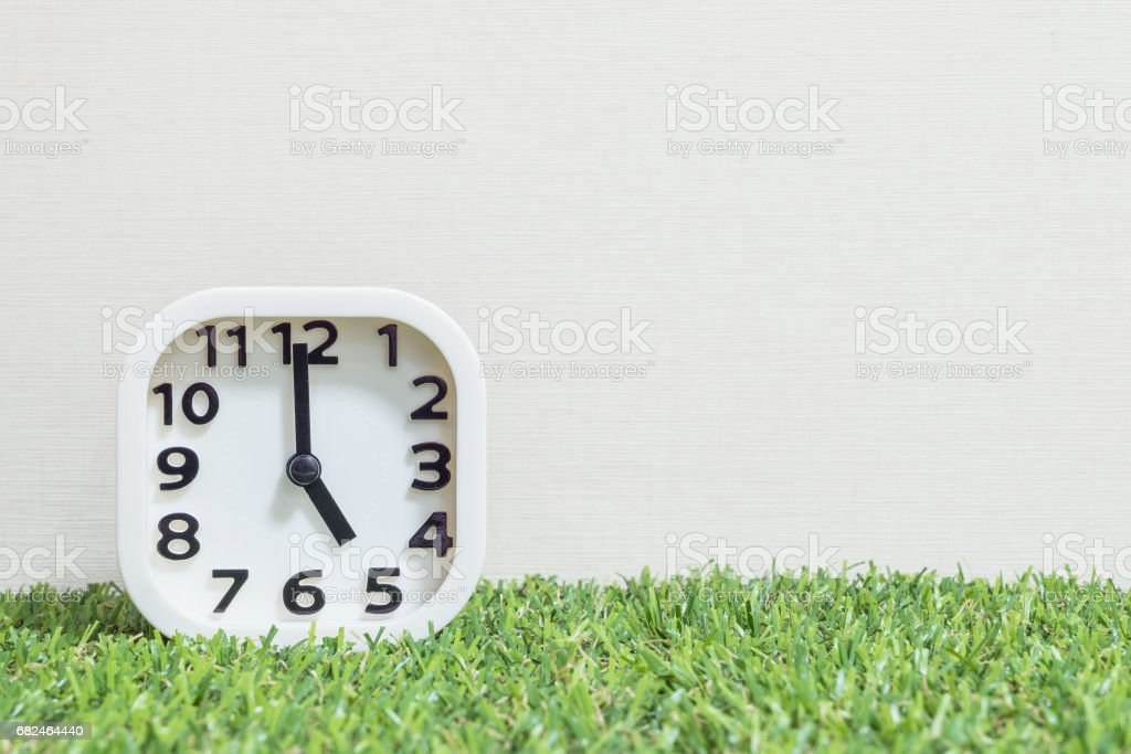 Closeup white clock for decorate in 5 o'clock on green artificial grass floor and cream wallpaper textured background with copy space royalty-free stock photo