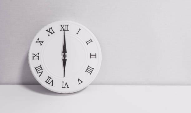 closeup weiße uhr zum dekorieren in 06:00 auf weißem holz schreibtisch und wallpaper strukturiertem hintergrund in schwarz / weiß-ton mit textfreiraum - römisch 6 stock-fotos und bilder