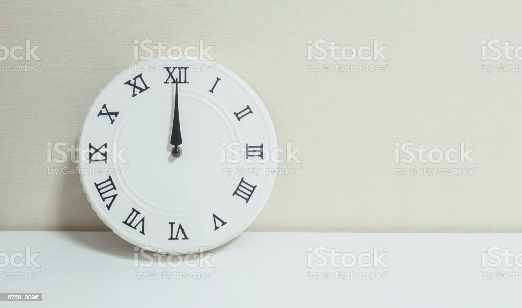 Closeup white clock for decorate show 12 a.m. on white wood desk and cream wallpaper textured background with copy space stock photo