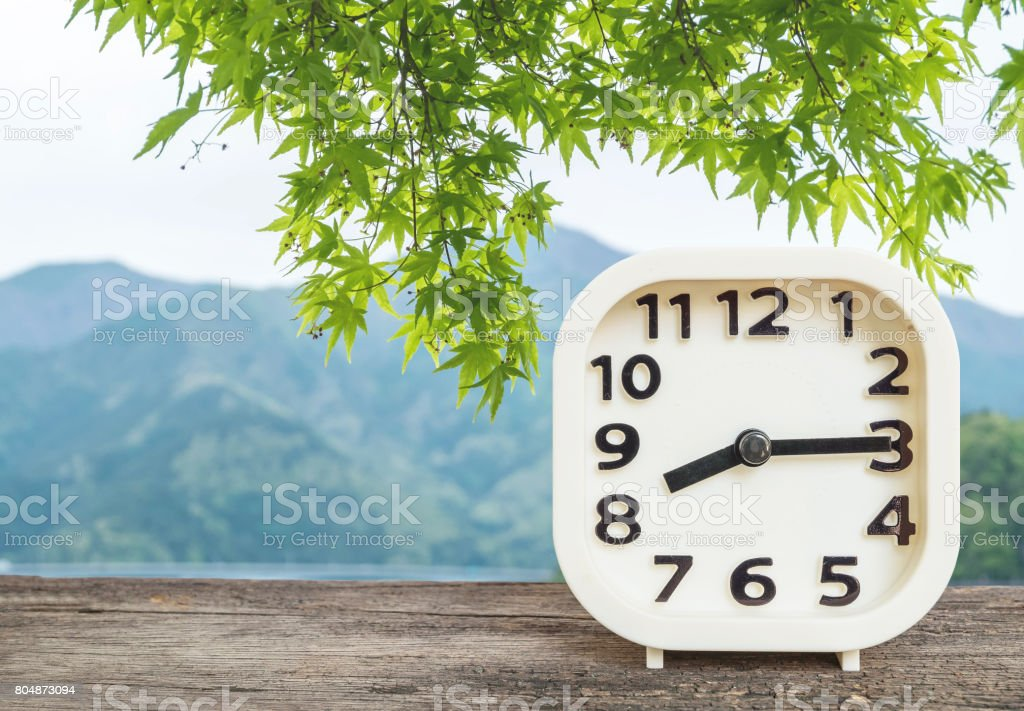 Closeup white clock for decorate show a quarter past eight o'clock or 8:15 a.m. on blurred mountain view background stock photo