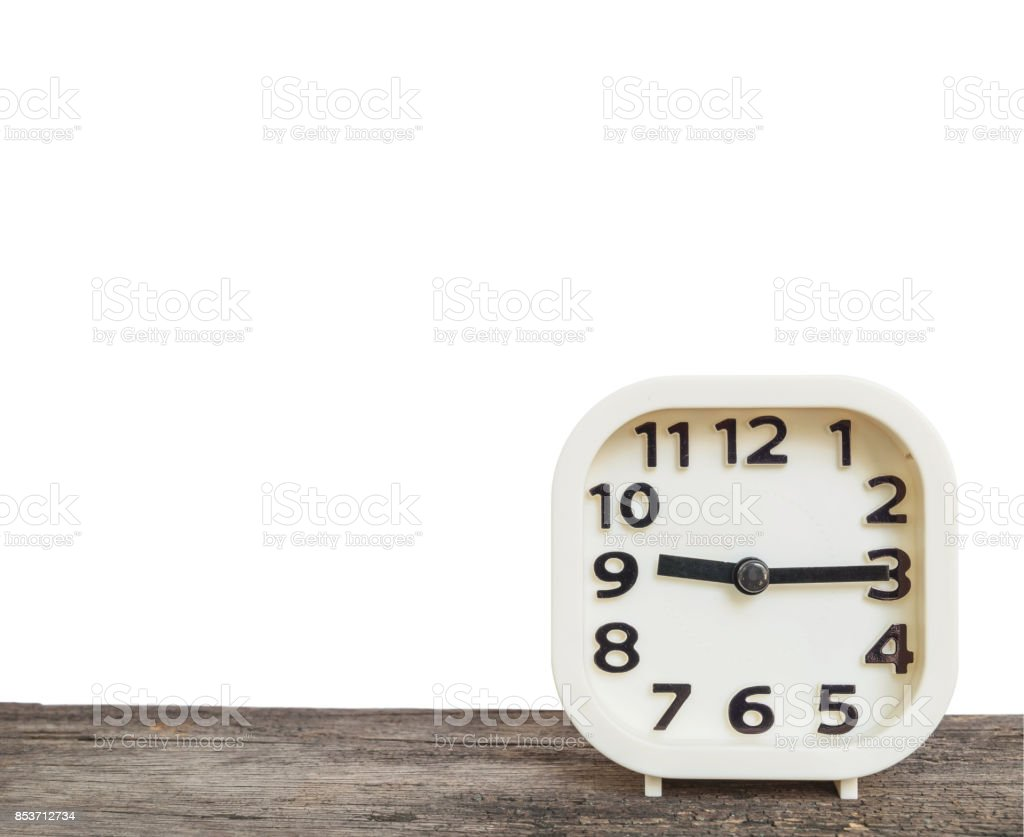 Closeup white clock for decorate show a quarter past nine o'clock or 9:15 a.m. on old brown wood desk isolated on white background with copy space stock photo