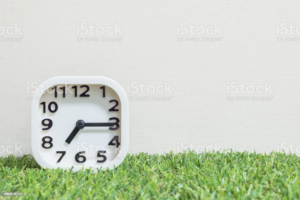 Closeup white clock for decorate show a quarter past seven or 7:15 a.m. on green artificial grass floor and cream wallpaper textured background with copy space stock photo