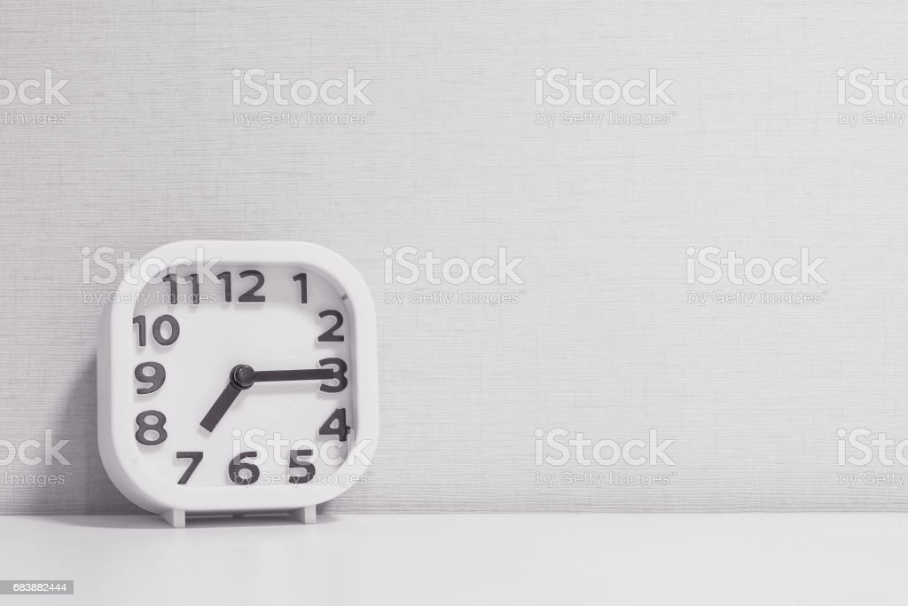 Closeup white clock for decorate show a quarter past seven or 7:15 a.m. on white wood desk and cream wallpaper textured background in black and white tone with copy space stock photo