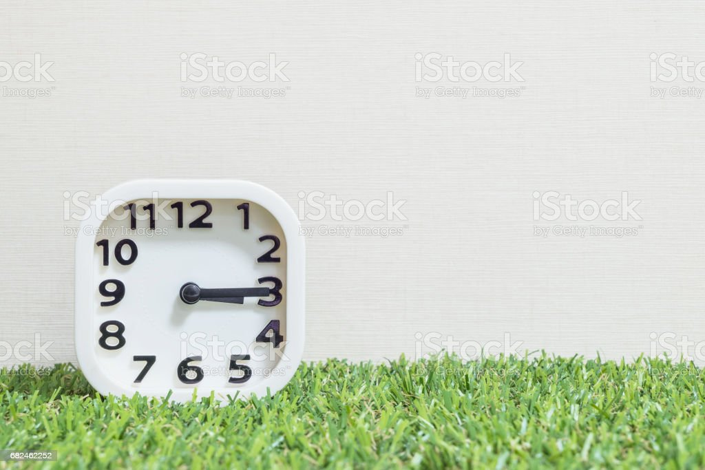 Closeup white clock for decorate show a quarter past three o'clock or 3:15 p.m. on green artificial grass floor and cream wallpaper textured background with copy space stock photo