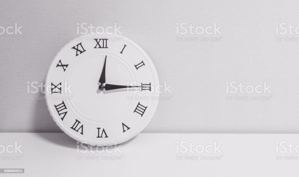 Closeup white clock for decorate show a quarter past twelve o'clock or 12:15 p.m. on white wood desk and wallpaper textured background in black and white tone with copy space stock photo