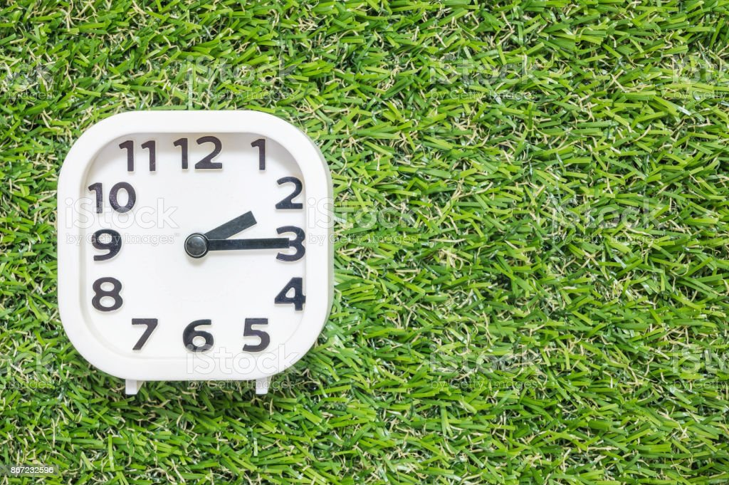 Closeup white clock for decorate show a quarter past two o'clock or 2:15 p.m. on green artificial grass floor textured background with copy space stock photo