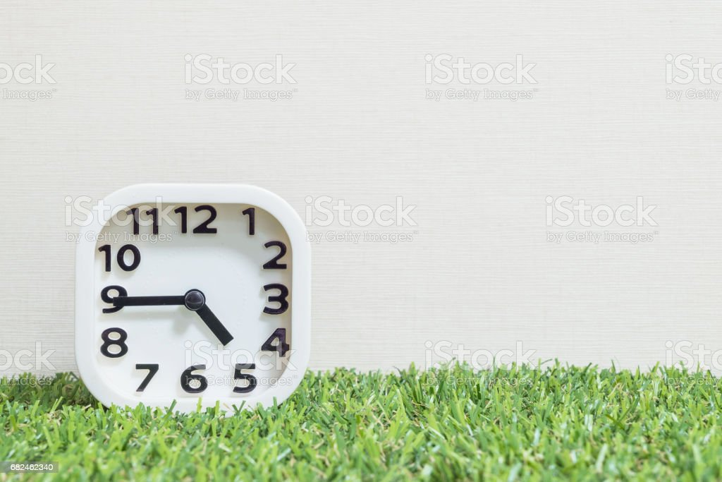 Closeup white clock for decorate show a quarter to five o'clock or 4:45 p.m. on green artificial grass floor and cream wallpaper textured background with copy space royalty-free stock photo
