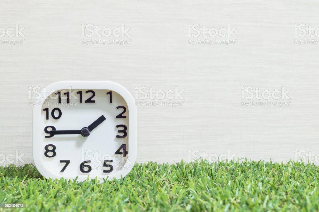 Reloj de primer plano blanco para decorar muestran un cuarto a 2:00 o 1:45 en césped artificial verde piso y crema papel pintado con textura de fondo con espacio de copia foto de stock libre de derechos