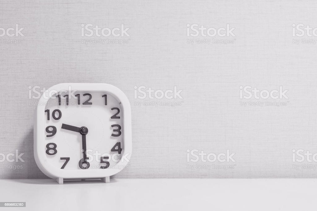Closeup white clock for decorate show half past nine or 9:30 a.m. on white wood desk and cream wallpaper textured background in black and white tone with copy space stock photo