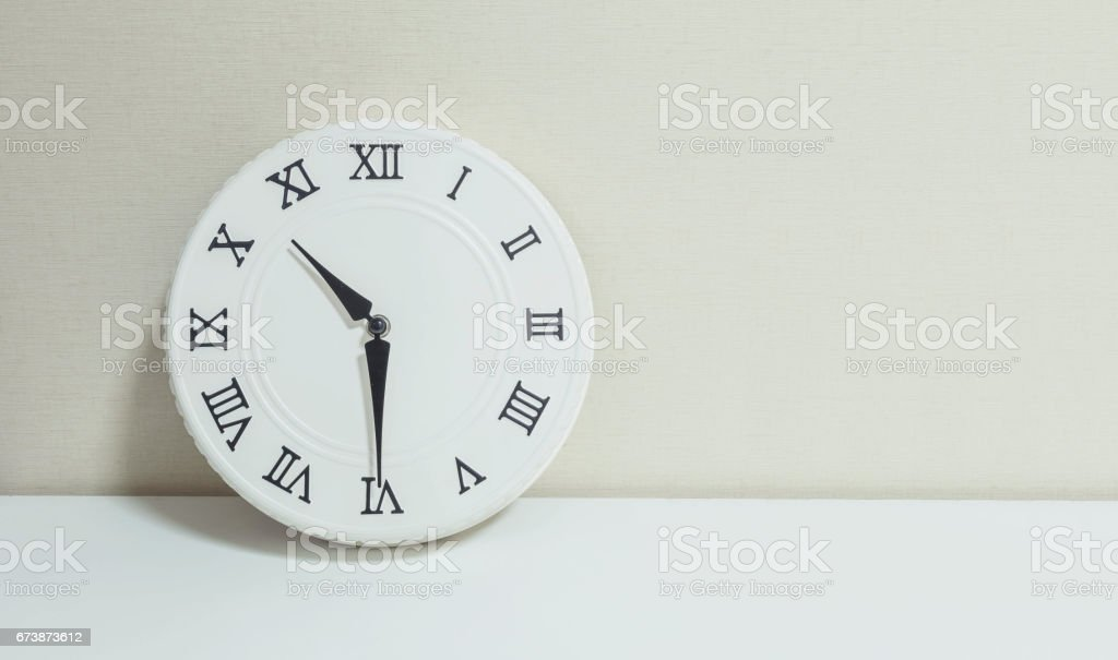 Closeup white clock for decorate show half past ten or 10:30 a.m. on white wood desk and cream wallpaper textured background with copy space stock photo