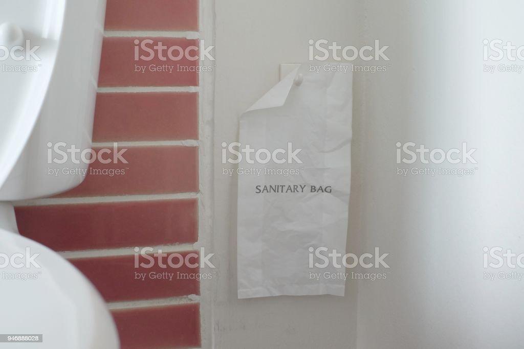 closeup white pastic sanitary bag for sanitaru napkin hanging in toilet stock photo