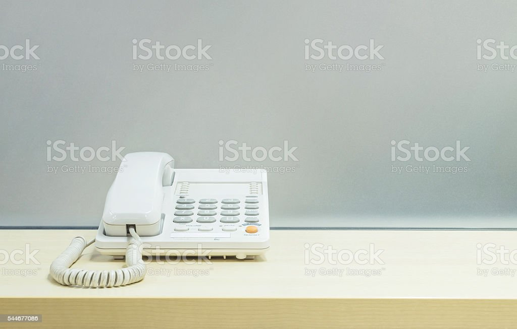 Closeup white phone , office phone on wooden desk stock photo