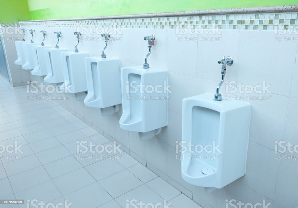 Closeup white urinals in men's bathroom, design of white ceramic urinals for men stock photo