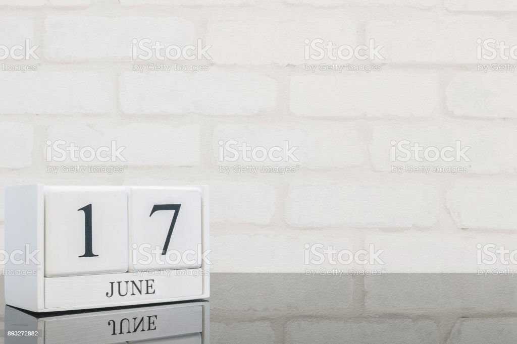 Closeup white wooden calendar with black 17 june word on black glass table and white brick wall textured background with copy space , selective focus at the calendar stock photo