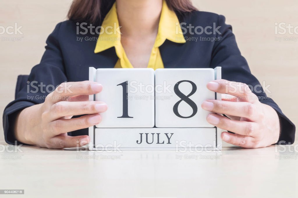 Closeup white wooden calendar with black 18 july word in blurred working woman hand on wood desk in office room , selective focus at the calendar stock photo