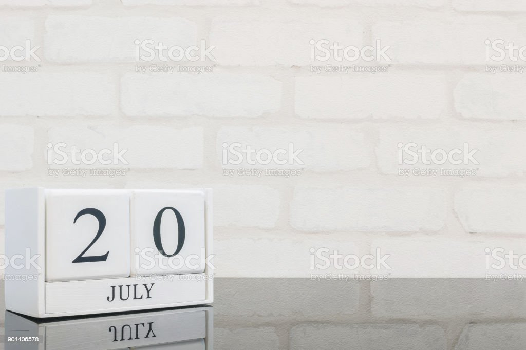 Closeup white wooden calendar with black 20 july word on black glass table and white brick wall textured background with copy space in selective focus at the calendar stock photo