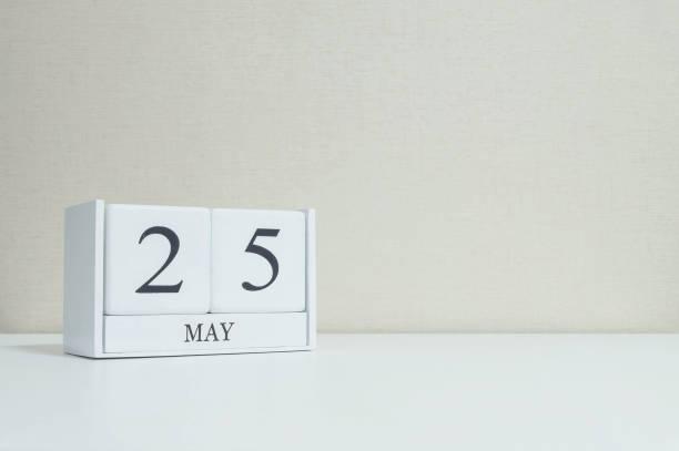 Primer plano blanco calendario de madera con negro 25 puede palabra en borroso blanco escritorio de madera y papel pintado de color crema en sala textura fondo con espacio de copia de enfoque selectivo en el calendario - foto de stock