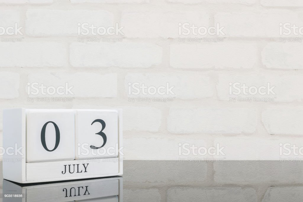 Closeup white wooden calendar with black 3 july word on black glass table and white brick wall textured background with copy space , selective focus at the calendar stock photo