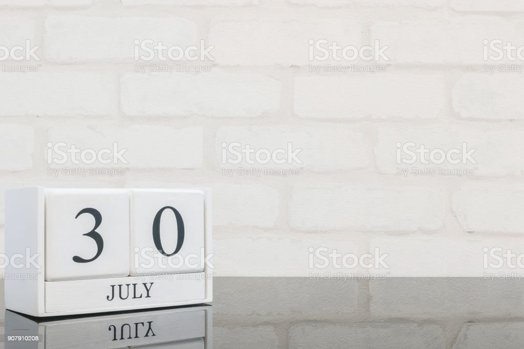 Closeup white wooden calendar with black 30 july word on black glass table and white brick wall textured background with copy space in selective focus at the calendar stock photo