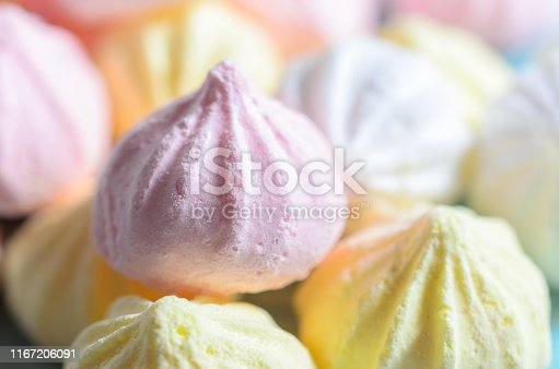 Closeup white, yellow and pink meringues . Sweet food background