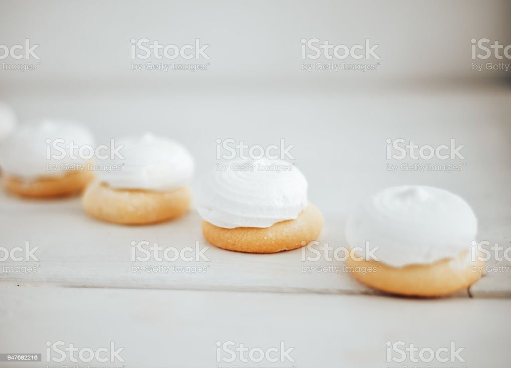 closeup white zephyr cookies lie to the line on white wooden background stock photo