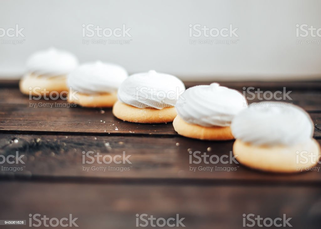 closeup white zephyr cookies lie to the line on wooden background stock photo
