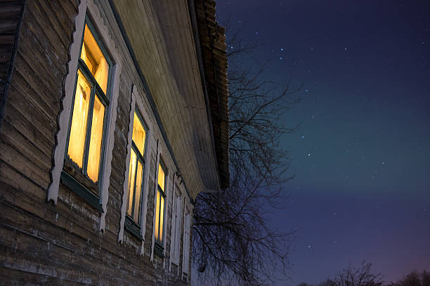 Closeup windowsof cozy old russian village house in the bitter Warm light from windows cozy old russian village house in the bitter cold. Winter night landscape with snow, stars, smoke from furnace russian dacha stock pictures, royalty-free photos & images