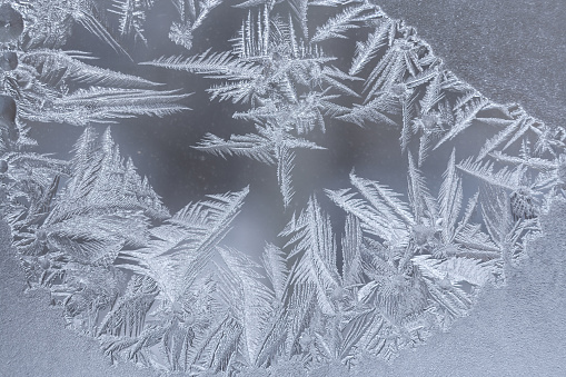 istock Close-up winter frosty pattern with  elongated pointed snowflakes on window . 1049923136
