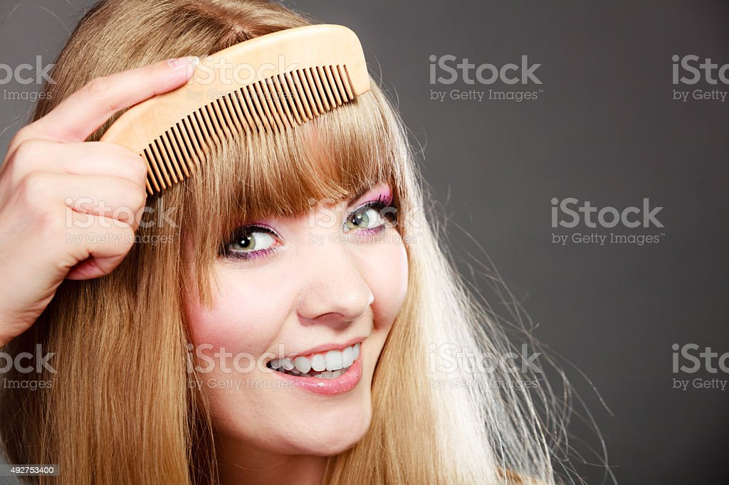 Closeup woman combing her fringe with comb stock photo