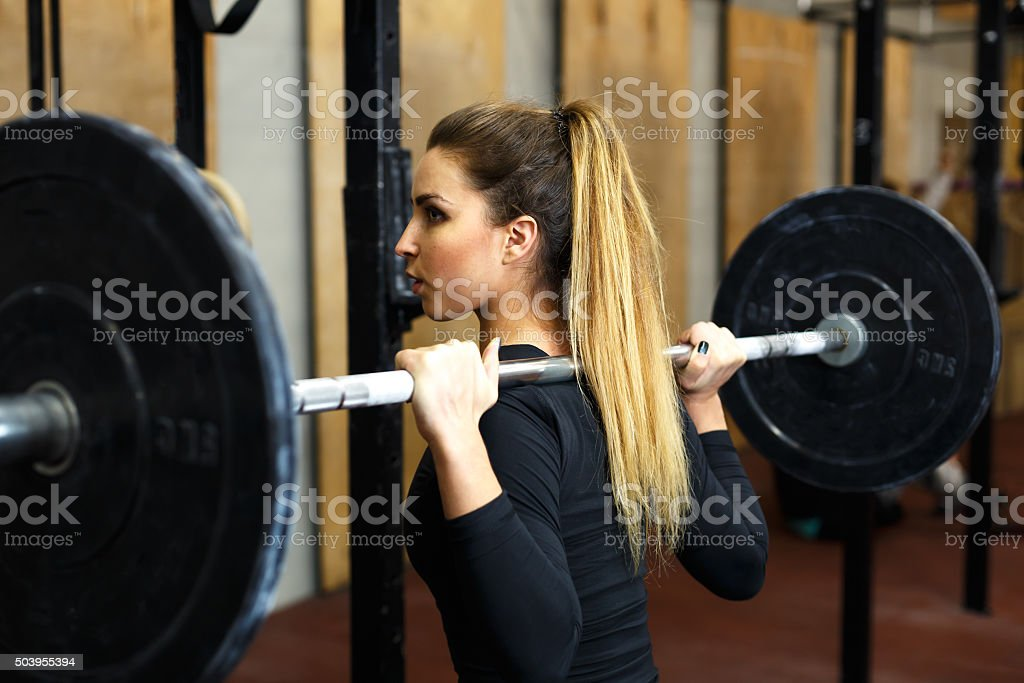 Closeup woman concentrated by doing squat stock photo