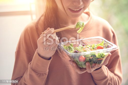closeup woman eating healthy food salad, focus on salad and fork