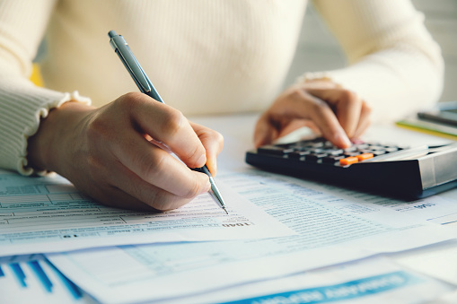 Closeup woman filling form of Individual Income Tax Return,