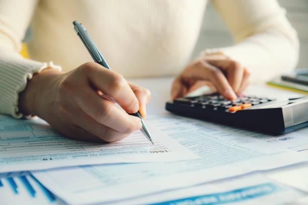 wanita closeup mengisi bentuk pengembalian pajak penghasilan individu, - cpa vs tax advisor potret stok, foto, & gambar bebas royalti