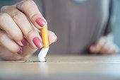 istock closeup woman hand destroying cigarette stop smoking concept 1275833242