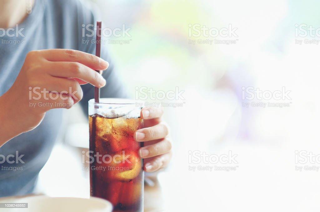 Closeup Frau Hand halten Glas Cola zu trinken im Restaurant Hintergrund, Frau Hand Glas Softdrinks mit Eis – Foto