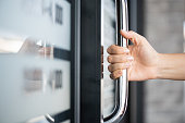 istock Closeup woman hand holding the door bar to open the door with glass reflection background. 1213375954