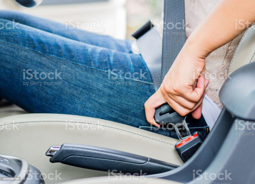 Closeup woman hand sitting inside car fastening seat belt. Safety belt safety first. stock photo