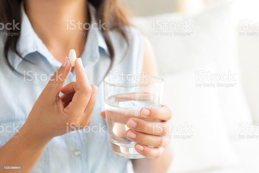 Closeup frau Hand mit Pillen Medizin Tabletten und ein Glas Wasser zur Behandlung von Kopfschmerzen. Gesundheitswesen, ergänzt medizinische Konzept. – Foto