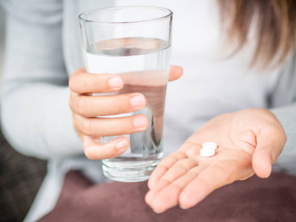 Closeup woman hand with pills medicine tablets and glass of water for headache treatment. Healthcare, medical supplements concept stock photo