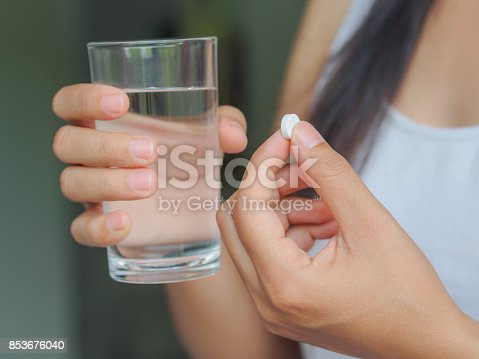 istock Closeup woman hand with pills medicine tablets and glass of water in her hands. Healthcare, medical supplements concept 853676040