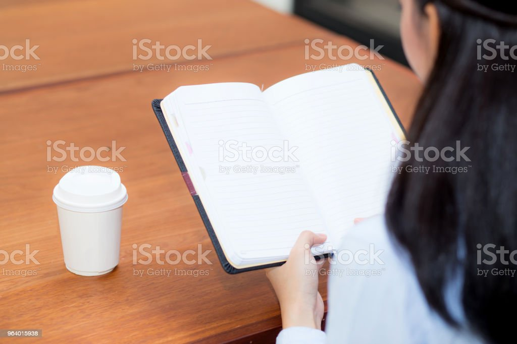 closeup woman hand writing on notebook on wooden table, girl work with paper at coffee shop, top view; freelance business concept. - Royalty-free Adult Stock Photo
